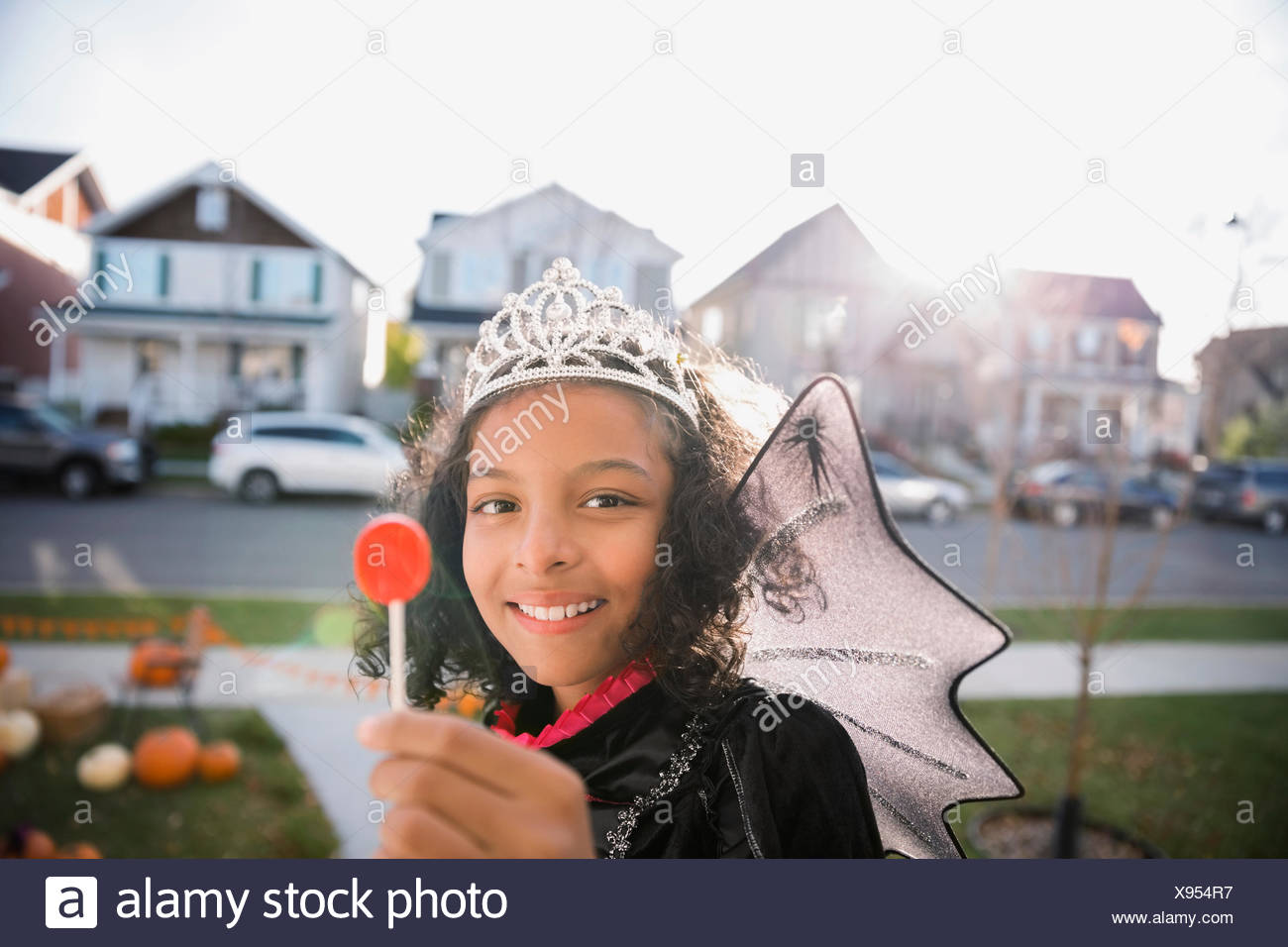 Portrait smiling girl Halloween princess costume enjoying lollipop - Stock Image