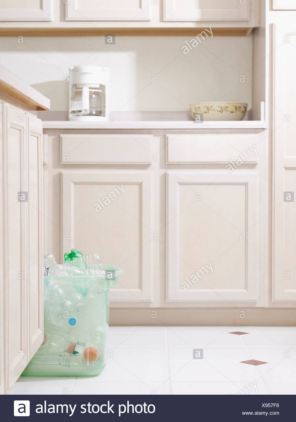 Bin of recyclable materials sitting on floor in kitchen - Stock Image