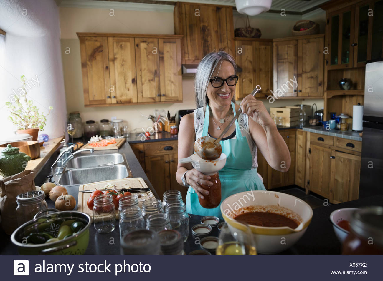 Smiling woman canning tomato sauce in kitchen - Stock Image