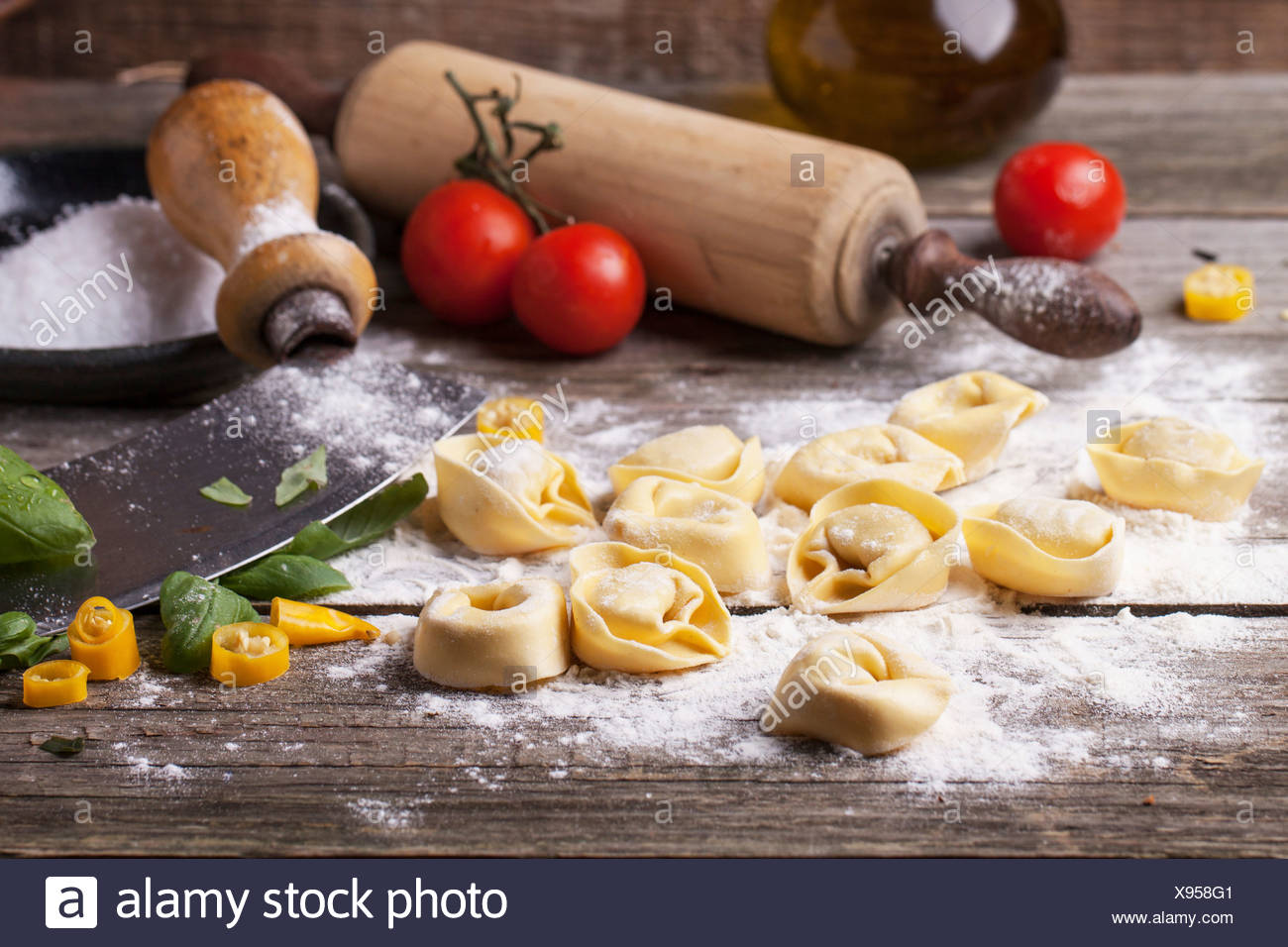 Homemade Pasta Ravioli On Old Wooden Table With Flour, Basil, Tomatoes And Vintage  Kitchen Accessories.