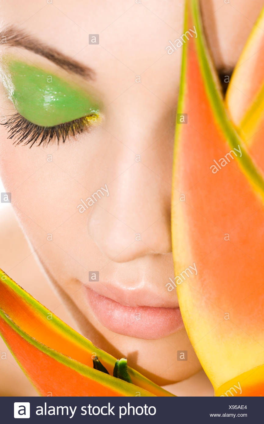 woman with green makeup and plant next to face Stock Photo