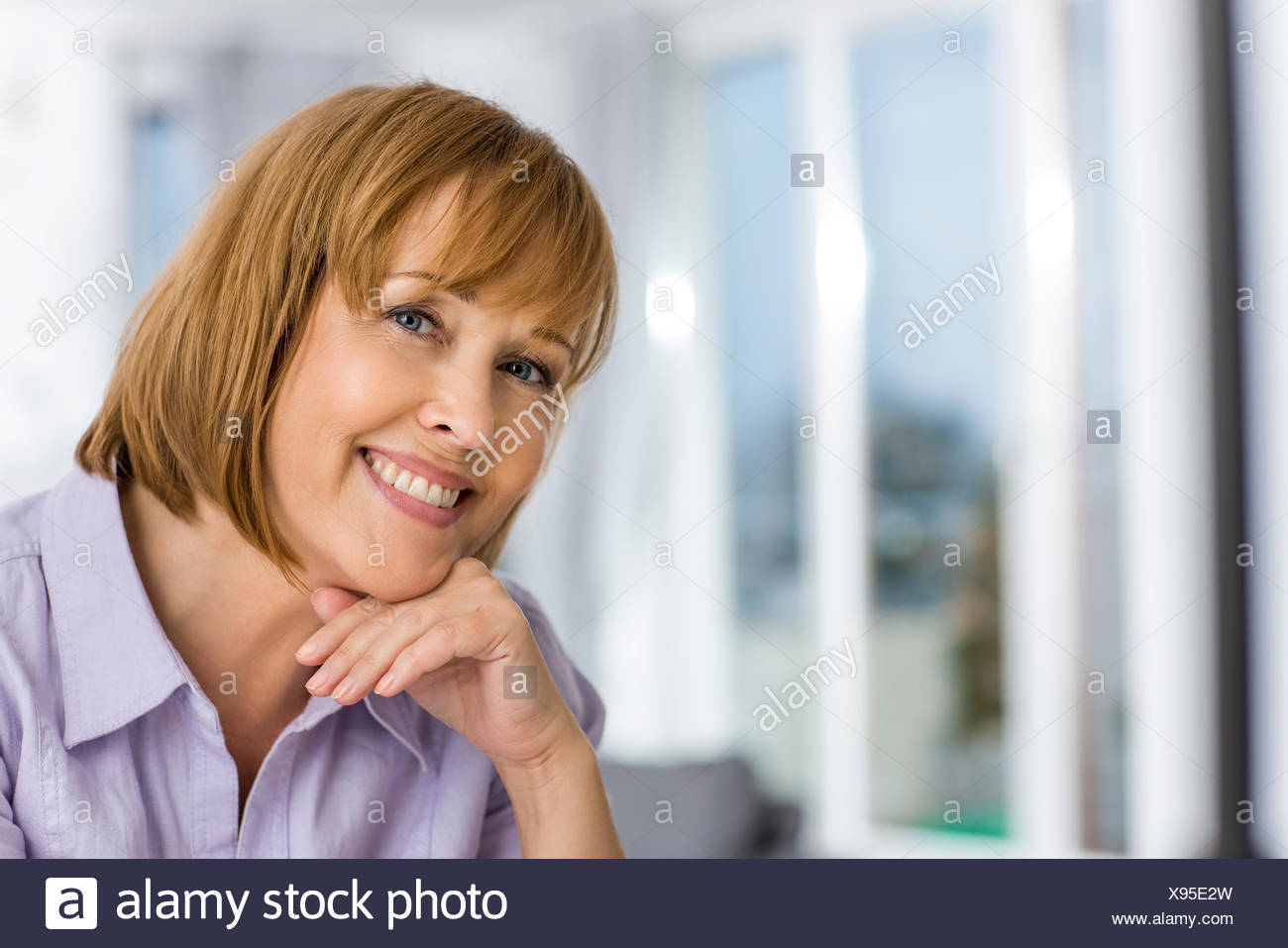 Portrait of happy woman with hand on chin at home - Stock Image