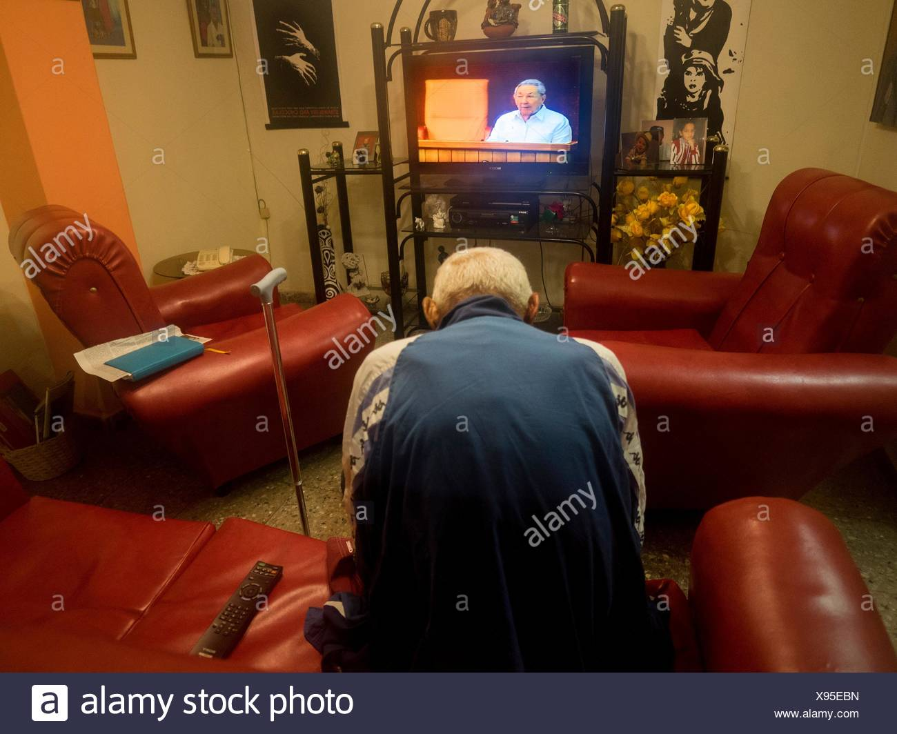 A man watches a speech by Raul Castro on television. - Stock Image