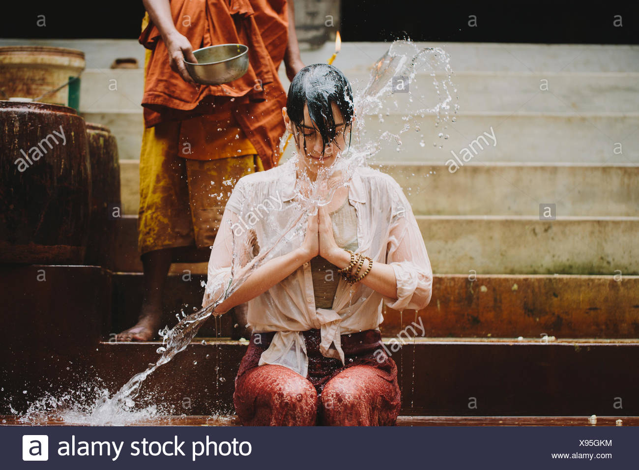 Cambodia, Buddhist monk water blessing young woman Stock Photo