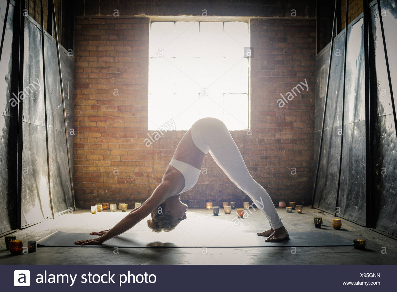 A blonde woman, in a white crop top and leggings, bending down on the floor surrounded by candles, in a yoga position. - Stock Image