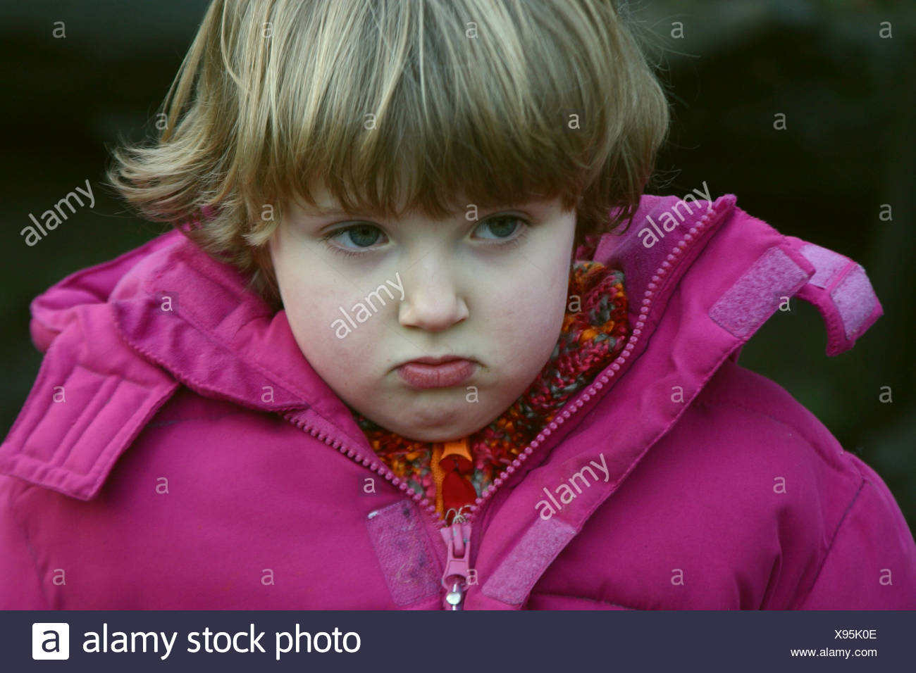 Pouty face from a pouting toddler girl outside in winter wear. - Stock Image