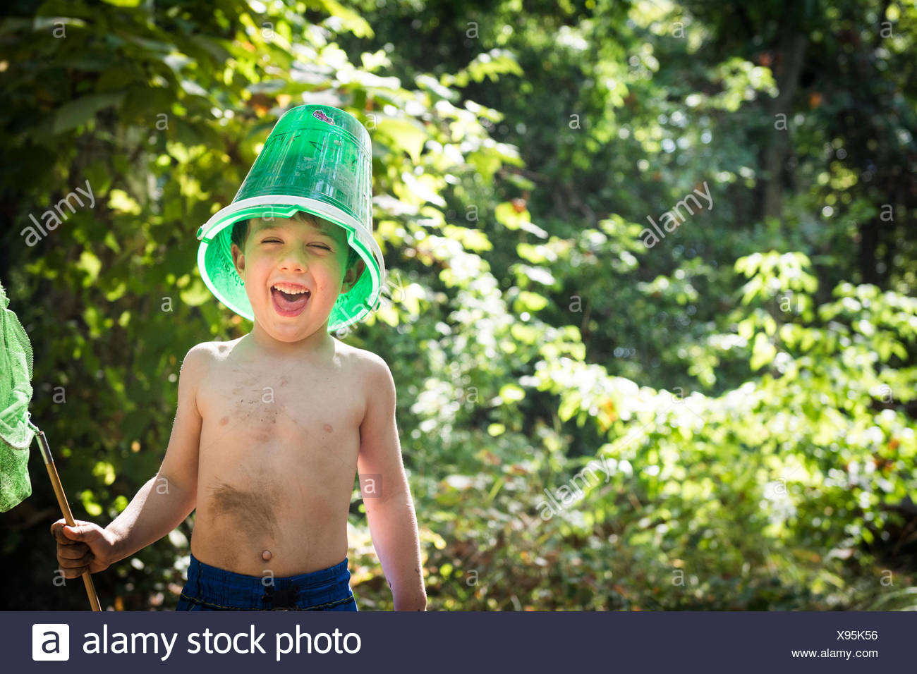 Toddler boy jokes with a bucket on his head and butterfly net in hand while next to creek in Bidwell Park, Chico, California. - Stock Image