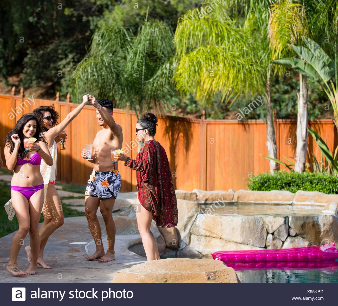 Young man dancing with sister in garden - Stock Image