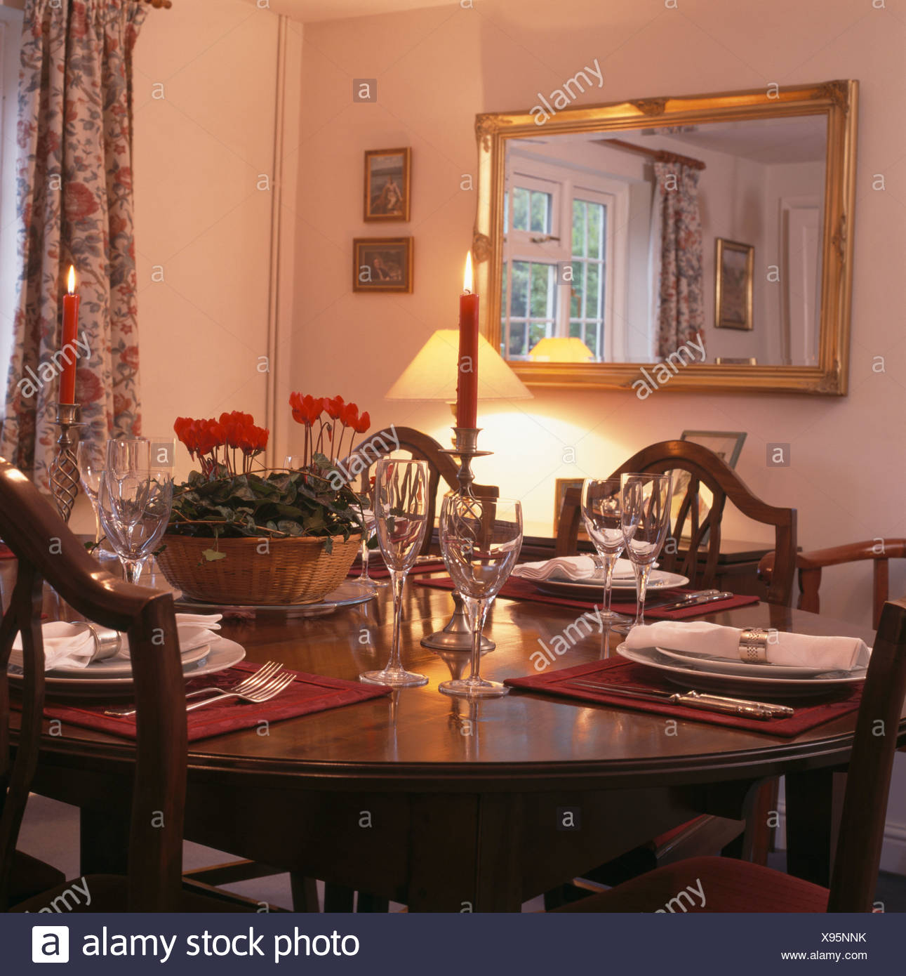 Rectangular Gilt Mirror In Traditional Dining Room With Wine Glasses And Place Settings On Table With Bowl Of Red Cyclamen Stock Photo Alamy