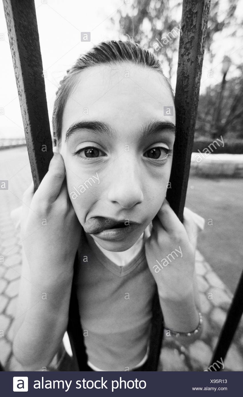 Young girl´s face caught in bars - Stock Image