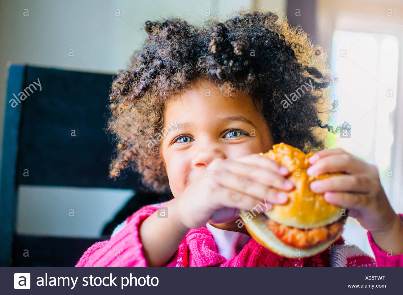 Portrait of cute girl eating hamburger in kitchen - Stock Image