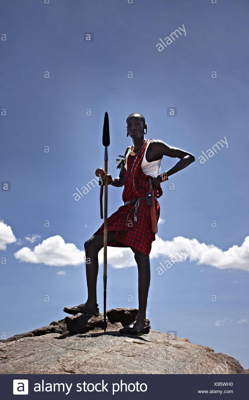 Maasai man standing on top of rock - Stock Image