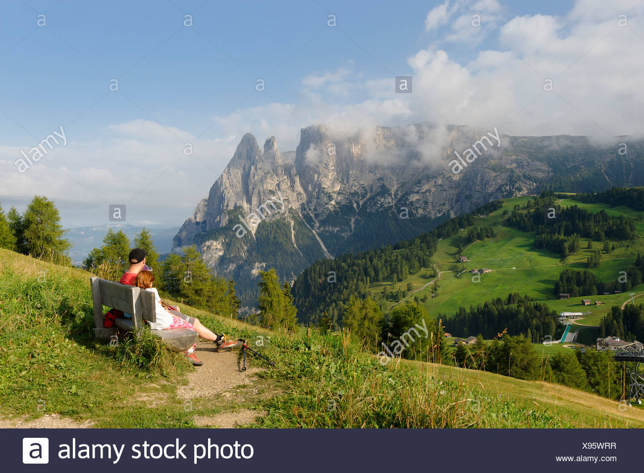 Hikers on Seiser Alm alpine pastures with Schlern Mountain, Alto Adige, Italy, Europe - Stock Image