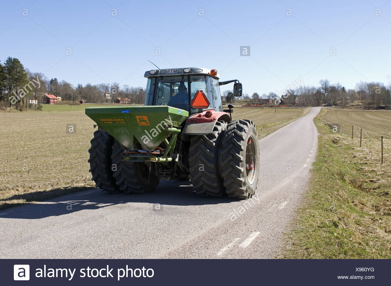 Tractor with Amazone ZA-F fertiliser spreader, driving along rural road, Sweden, spring Stock Photo