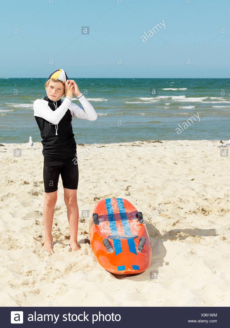 Portrait of boy nipper (child surf life savers) putting on cap, Altona, Melbourne, Australia - Stock Image