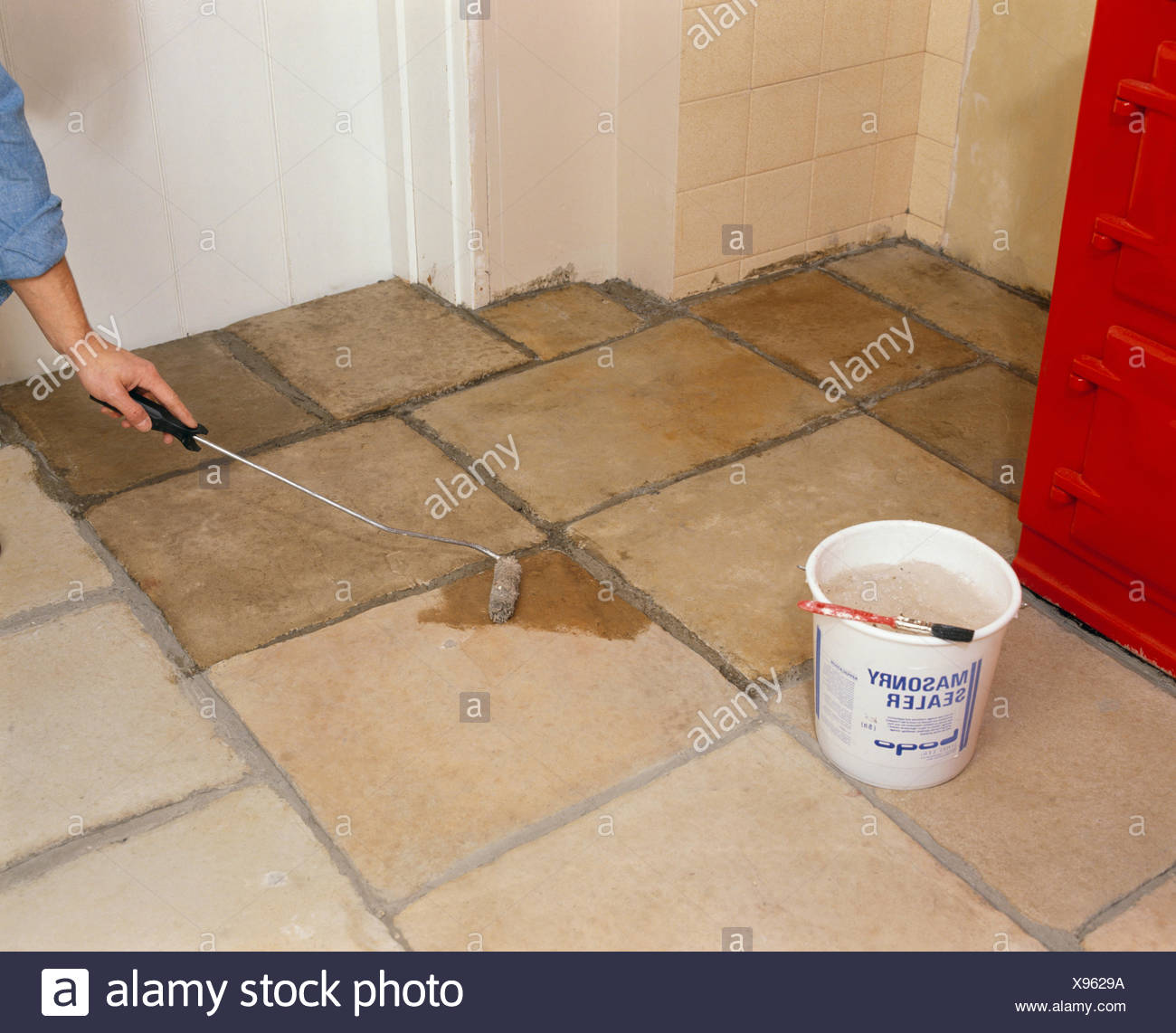 Close-up of man applying masonry sealer to newly tiled floor - Stock Image
