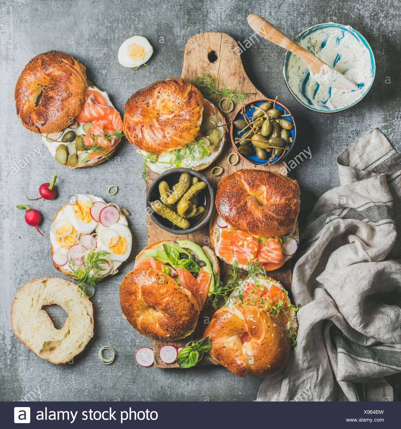 Variety of bagels with smoked salmon, eggs, radish, avocado, cucumber, greens and cream cheese in bowl for breakfast, lunch, party or takeaway on wood - Stock Image