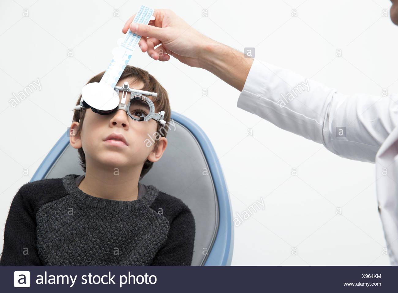 Optometrist examining eyesight of boy - Stock Image