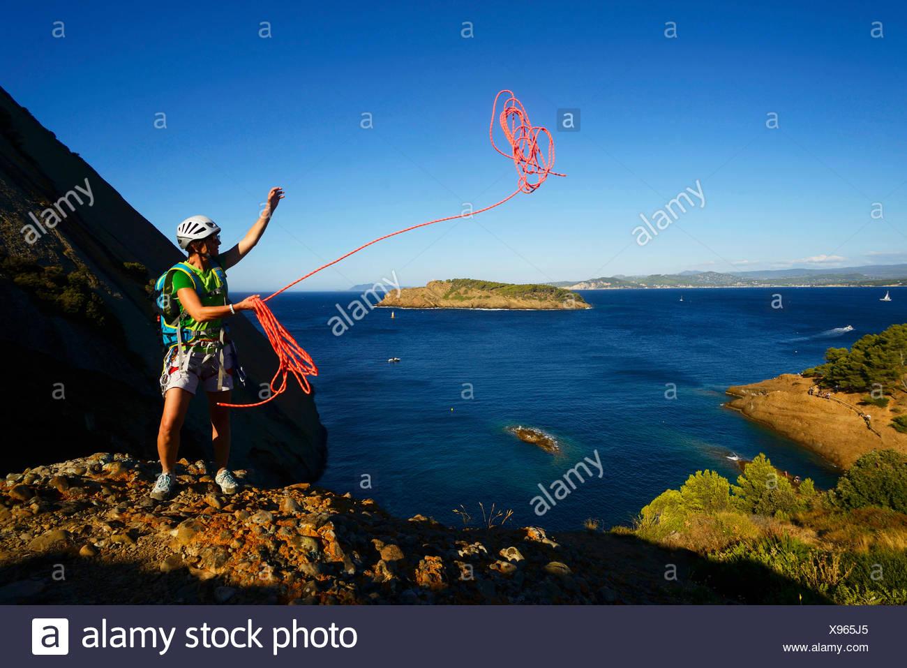 climber throwing a rope at coastal rock Bec de l'Aigle, adventure way, France, Provence, Calanques National Park, La Ciotat - Stock Image