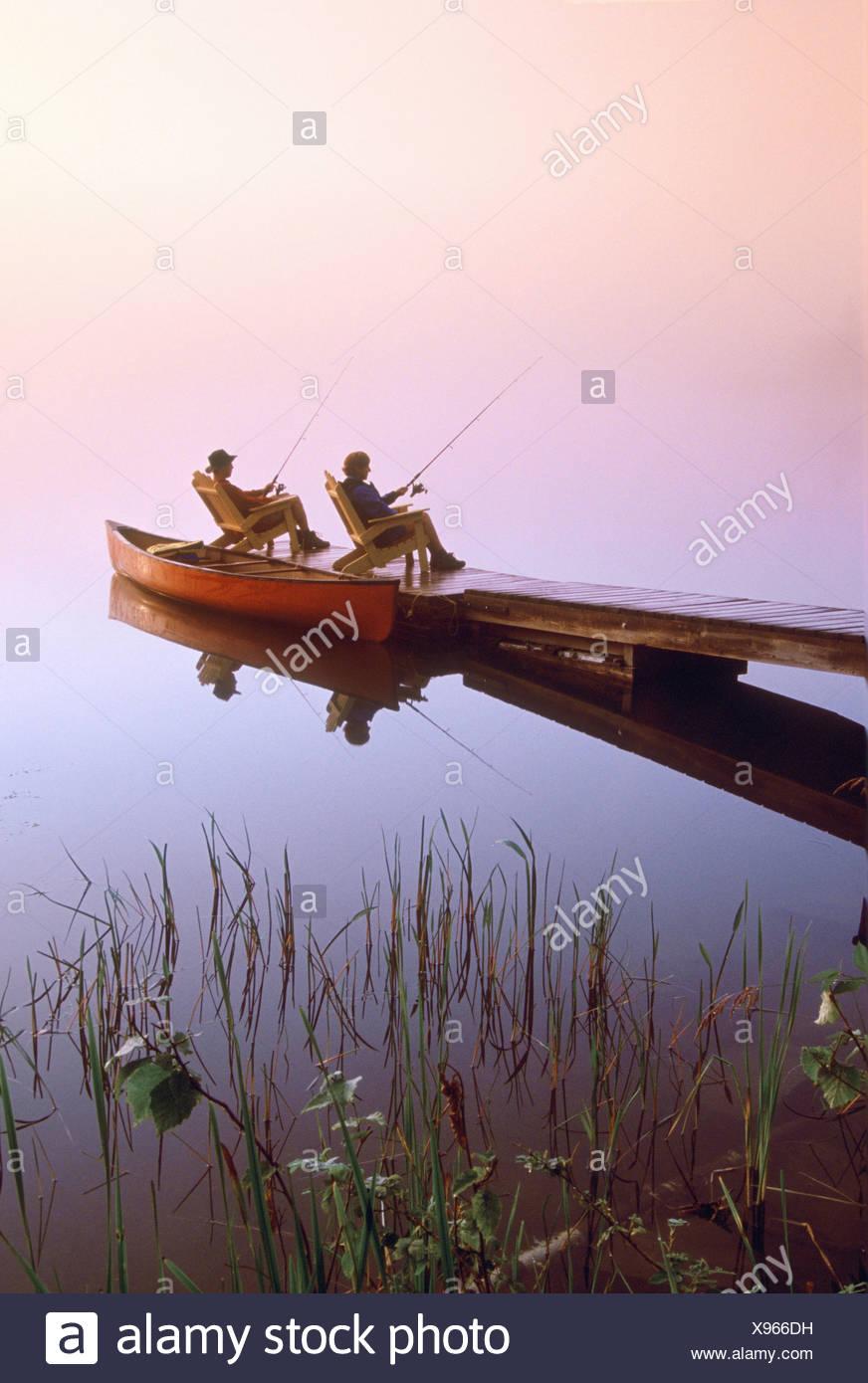 Couple Fishing off Dock, Winnipeg River, Pinawa, Manitoba - Stock Image
