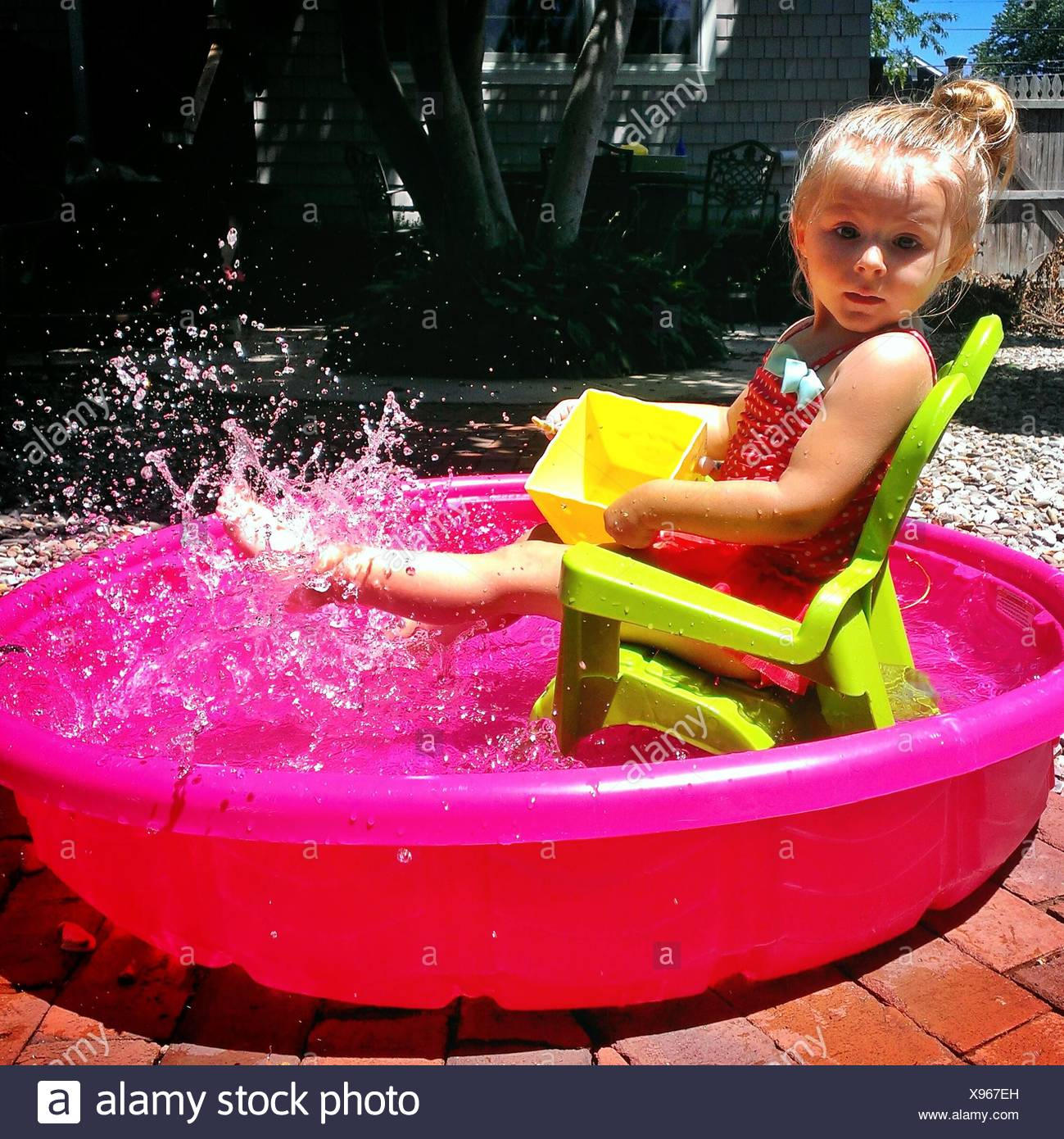 Side View Portrait Of A Cute Girl Splashing Water In Tub Outdoors - Stock Image