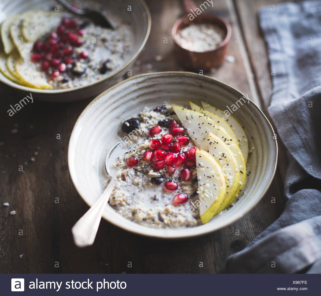 Seeded oatmeal (hemp, flax, chia, sunflower seed) with pear and pomegranate - Stock Image