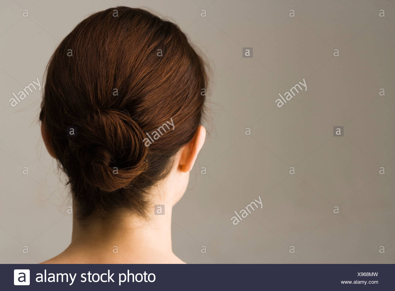 Woman with hair arranged in chignon, rear view - Stock Image