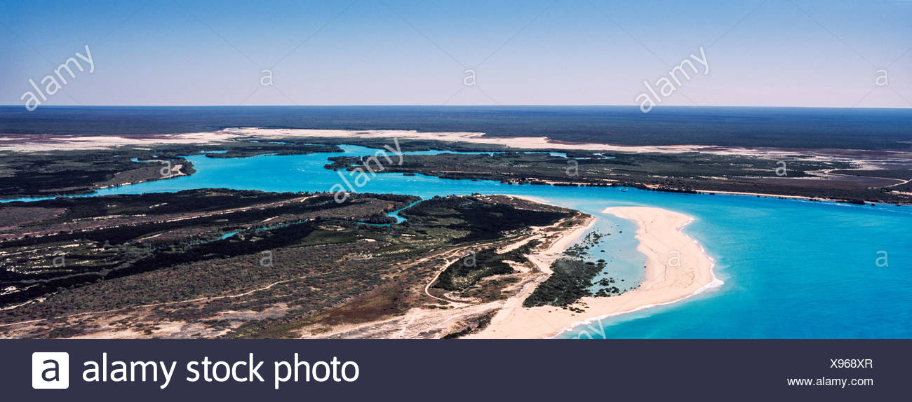 A winding turquoise tidal river flows inland from the sea. - Stock Image