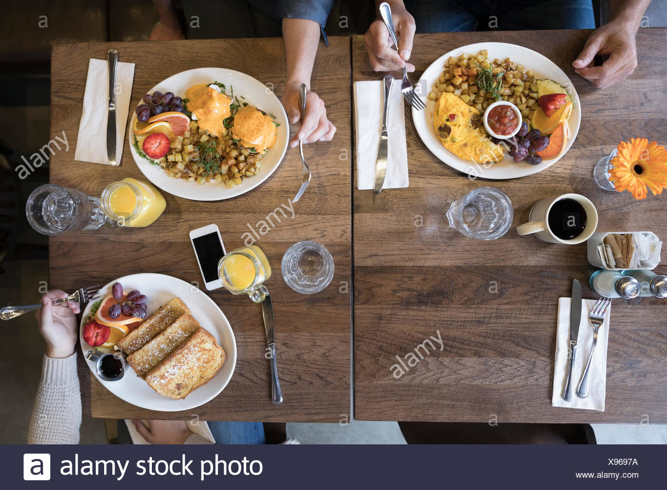 Overhead view family eating brunch at diner table - Stock Image