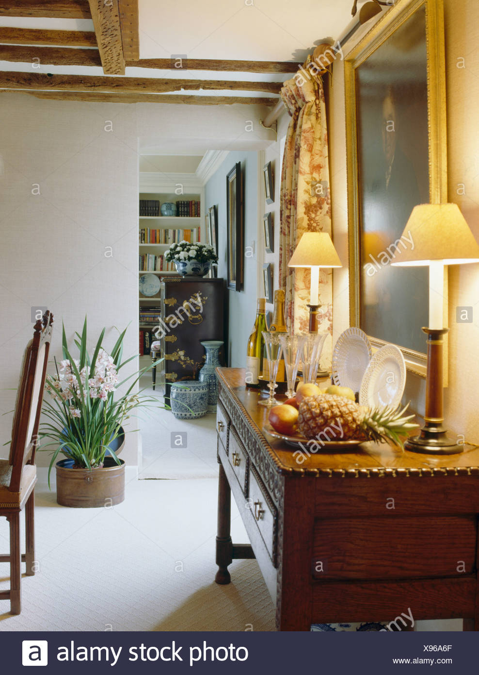 Sideways view of lighted lamps on console table in ...