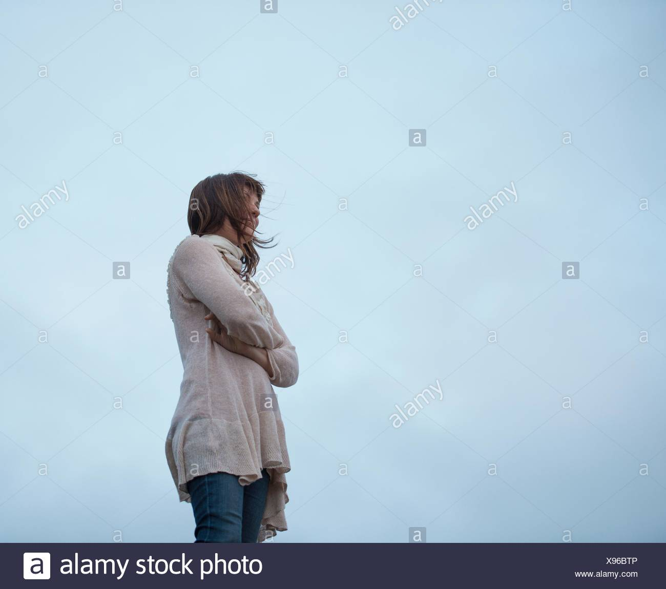 Low angle view of woman with arms folded and overcast sky - Stock Image