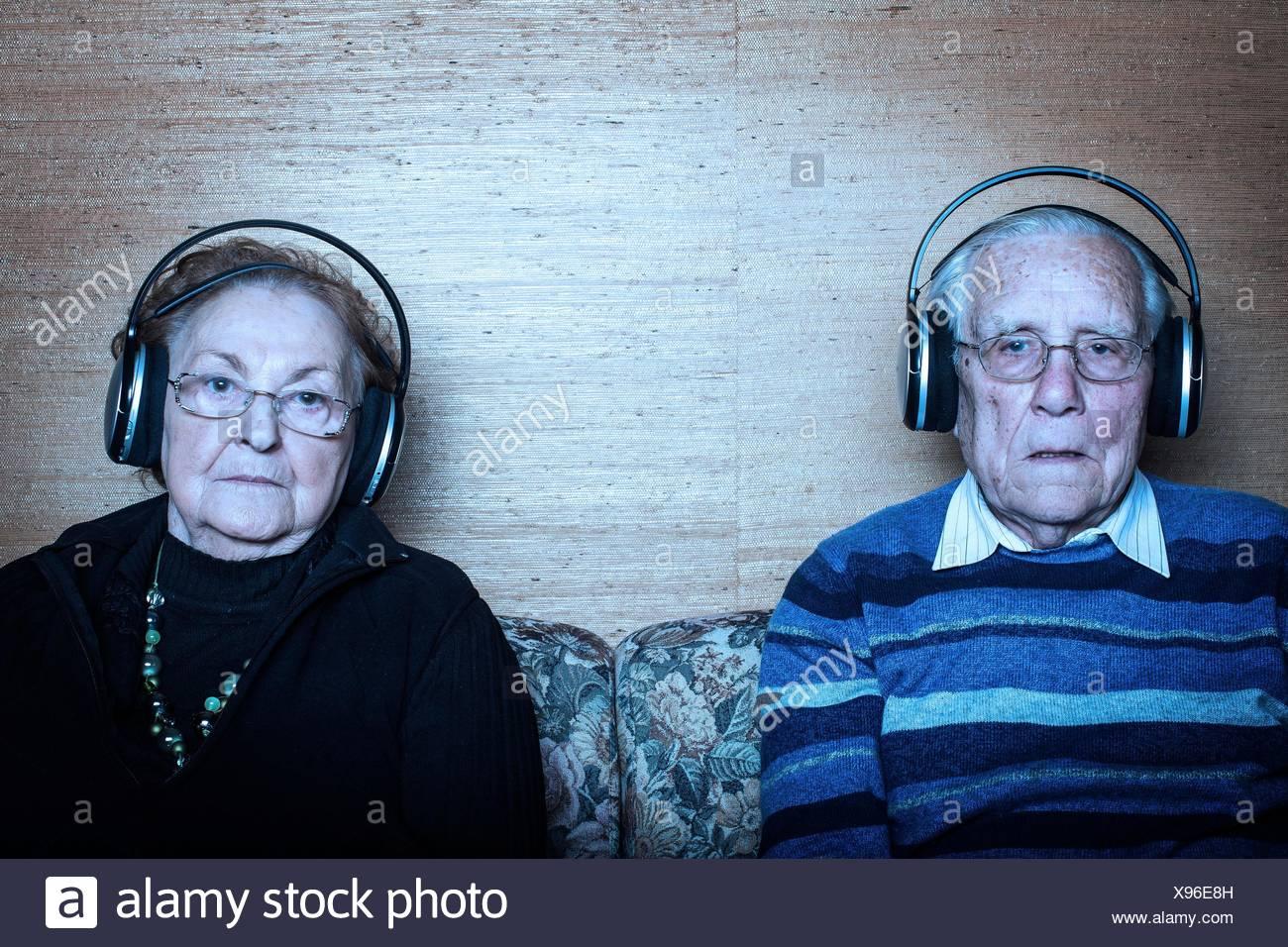 MODEL RELEASED. Senior couple sitting on sofa wearing headphones. - Stock Image