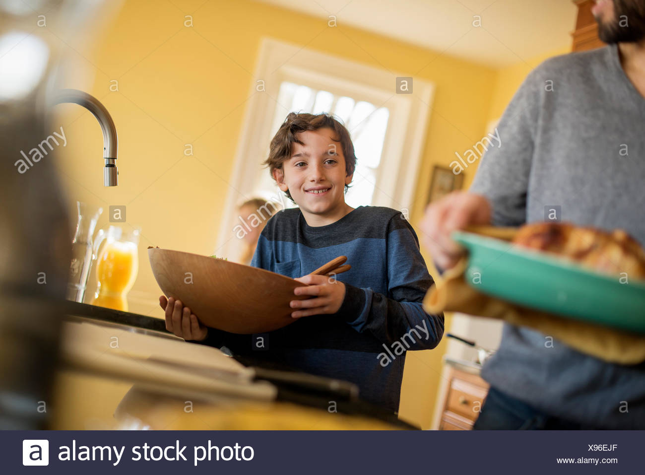 A woman carrying prepared food to the table. A boy with a large wooden bowl. - Stock Image