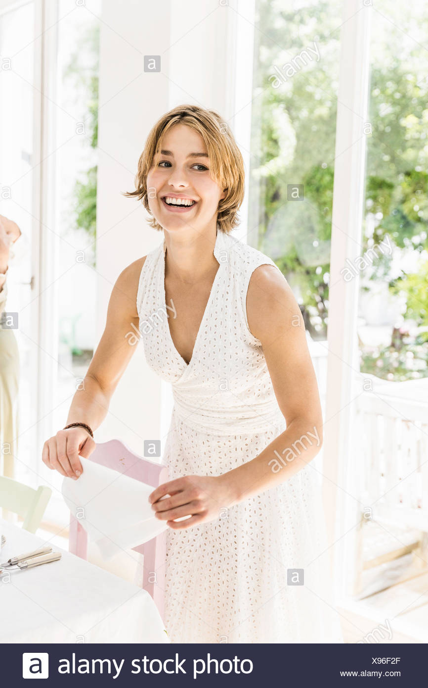 Woman folding napkins at dining room table for party - Stock Image