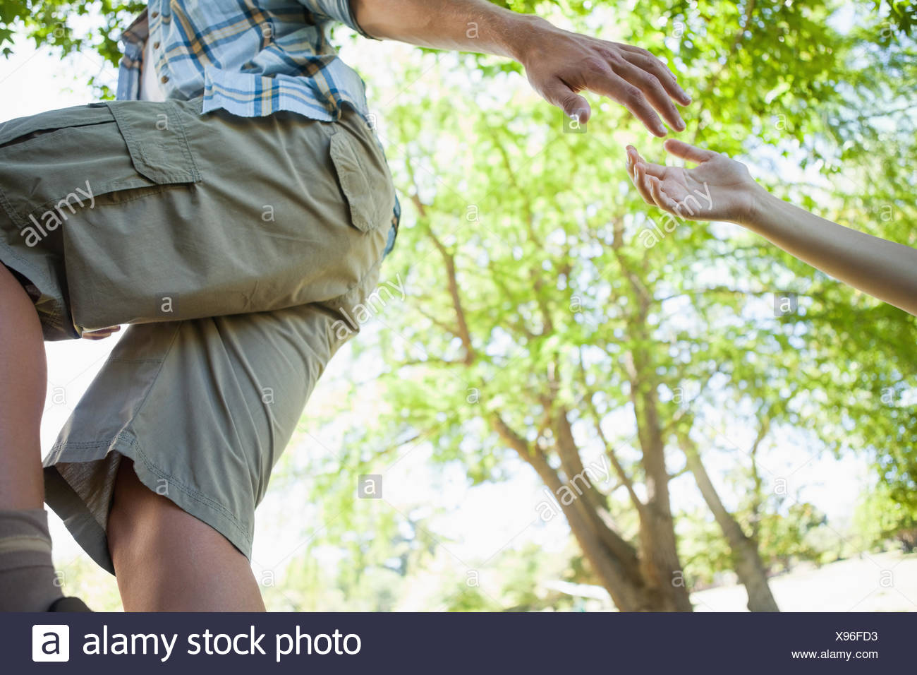 Man giving helping hand to girlfriend on hike - Stock Image