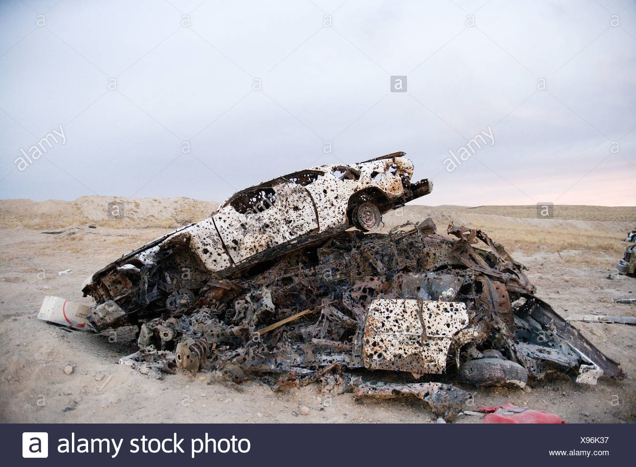 Car with bullet holes used for target practice - Stock Image