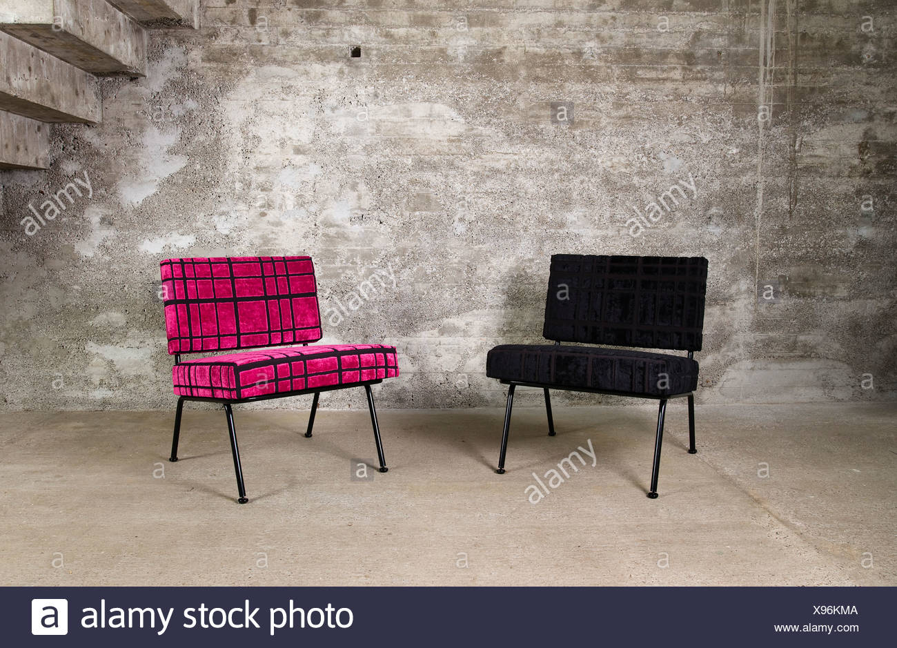 Two designer rocking chairs in an empty room in front of a concrete wall - Stock Image
