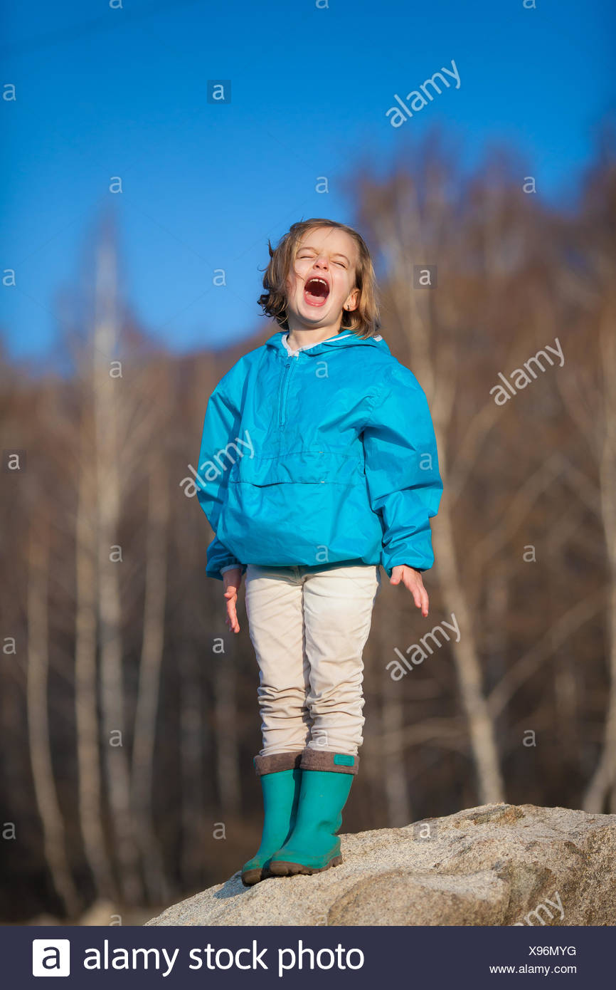Girl (4-5) standing on rock and shouting - Stock Image
