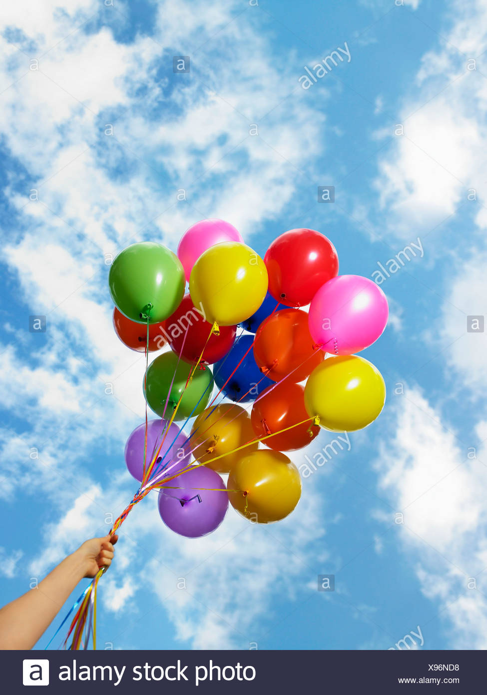 Hand holding colorful balloons - Stock Image