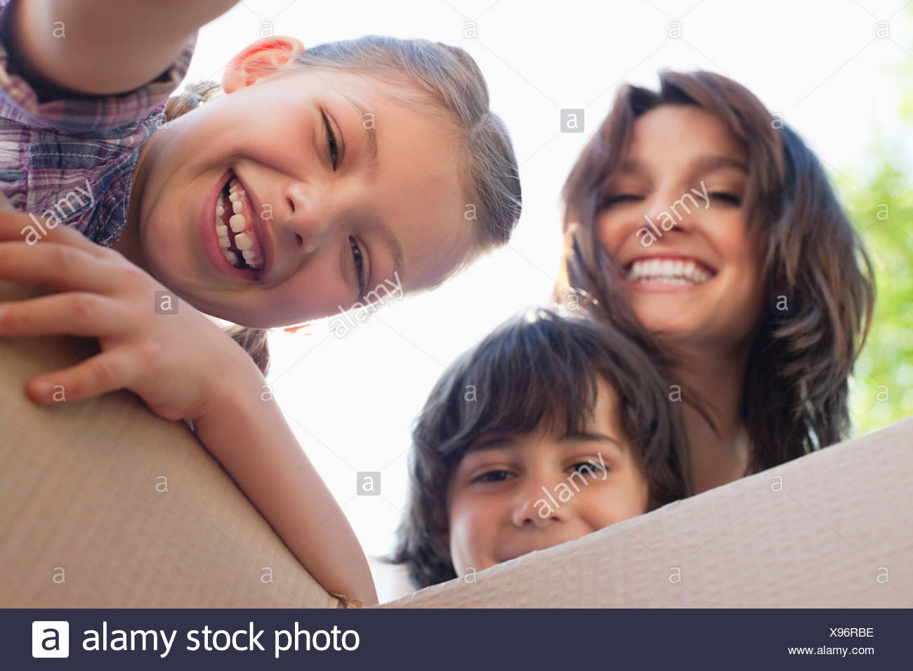 Portrait of smiling family looking into cardboard box - Stock Image