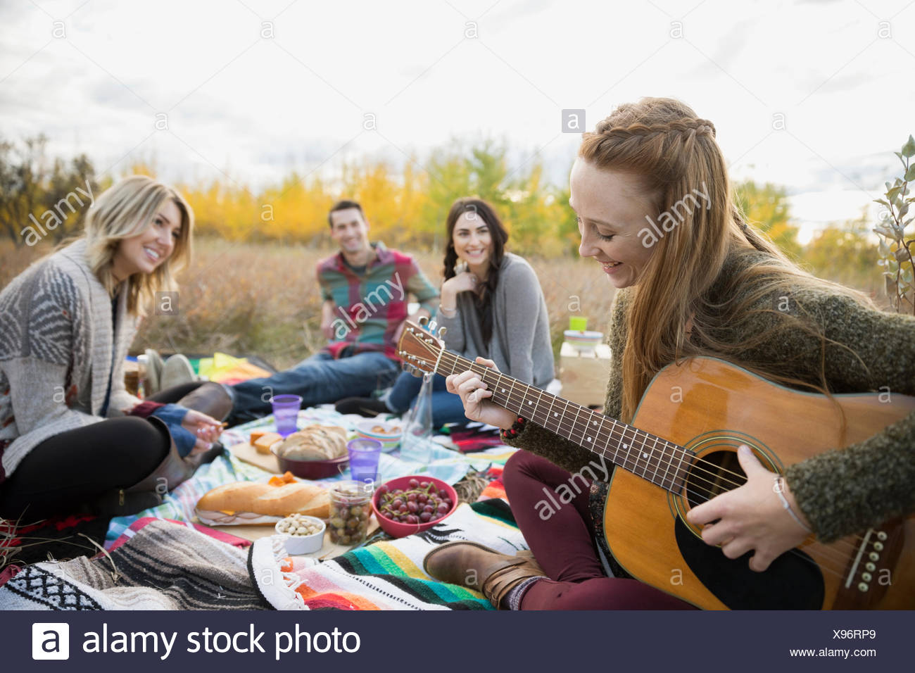 Young woman playing guitar at picnic with friends - Stock Image