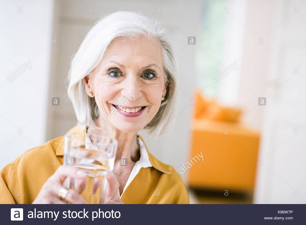 Portrait of senior woman holding tumbler of water looking at camera smiling - Stock Image