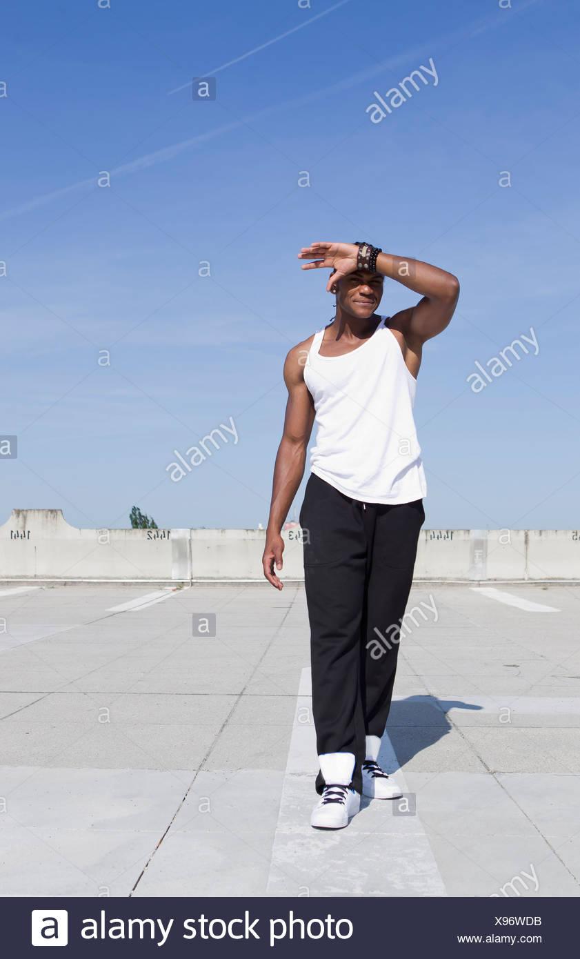 Man shielding his eyes on urban rooftop - Stock Image