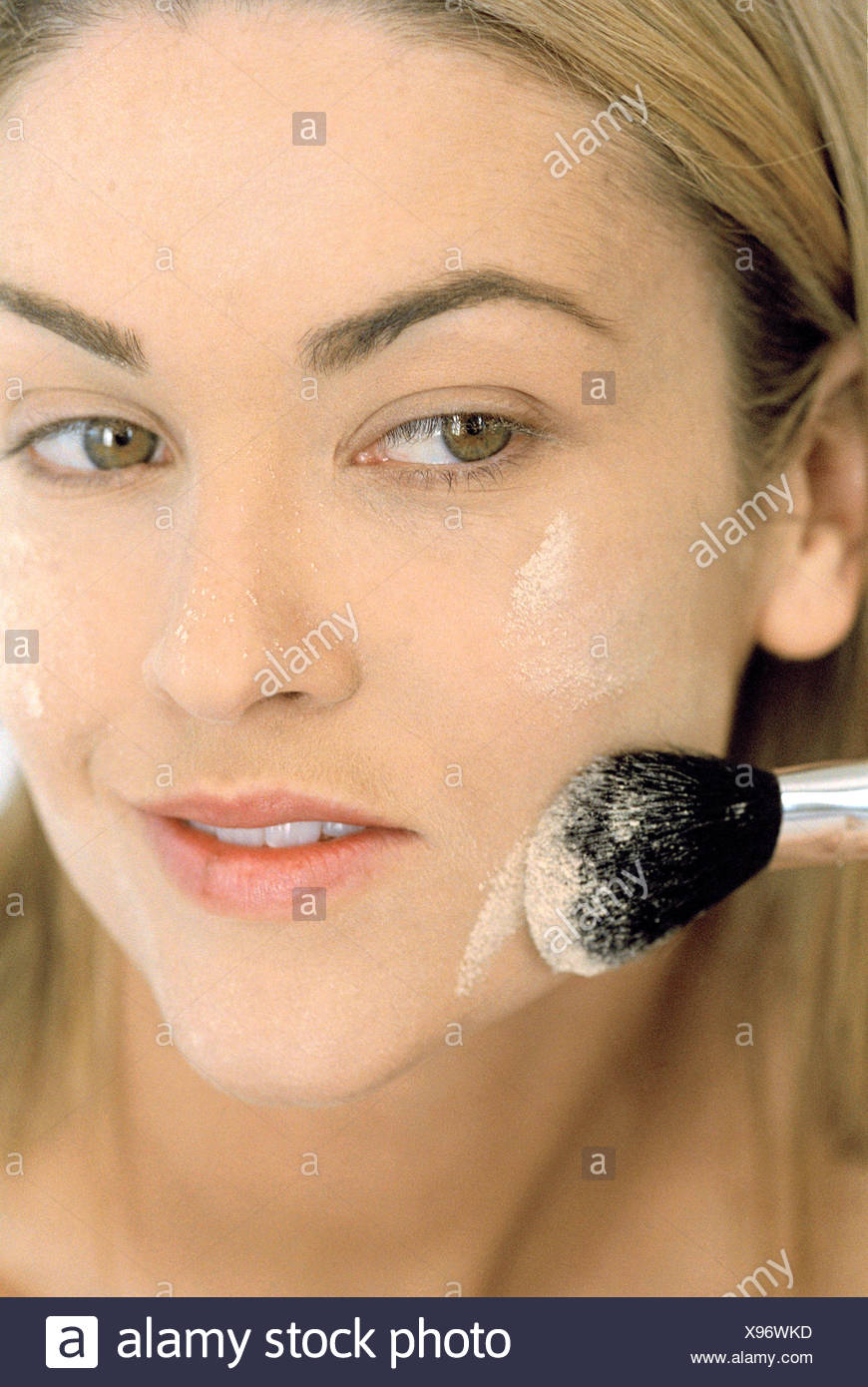 Female long straight blonde hair tucked behind ear applying powder face brush along chin, powder left on nose and cheeks - Stock Image