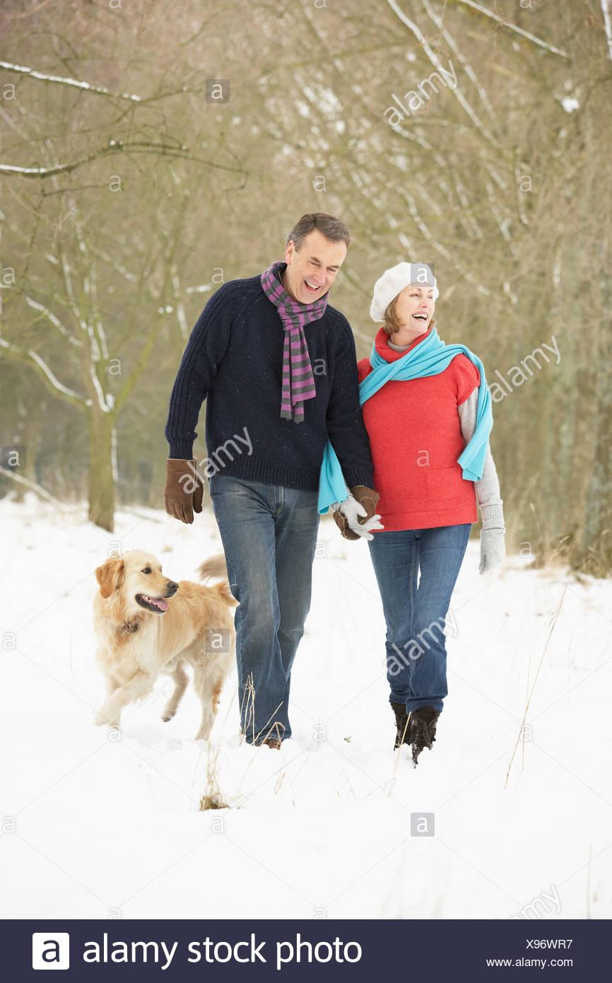 Senior Couple Walking Dog Through Snowy Woodland - Stock Image