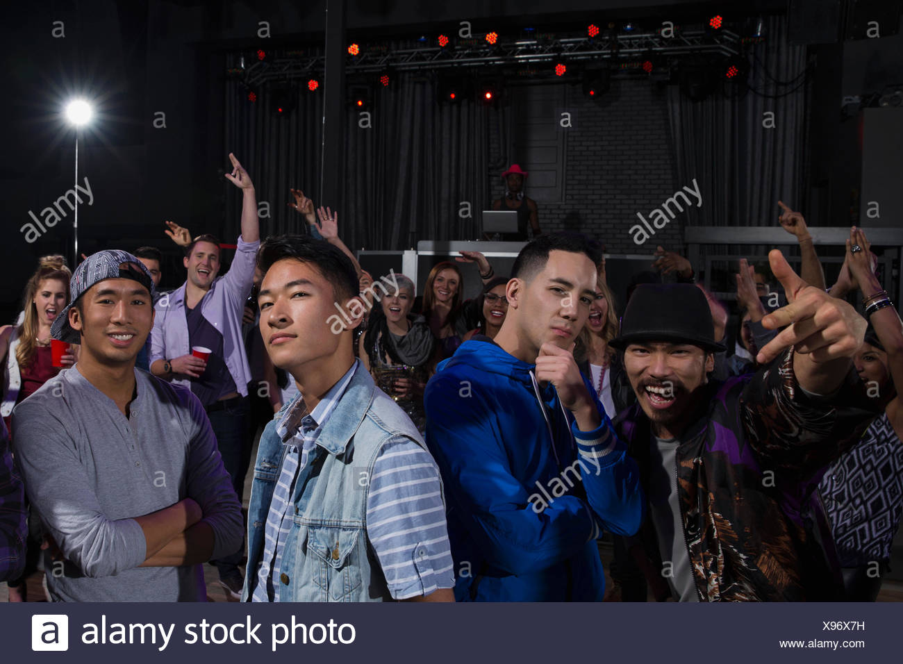 Portrait of confident men among crowd in nightclub - Stock Image
