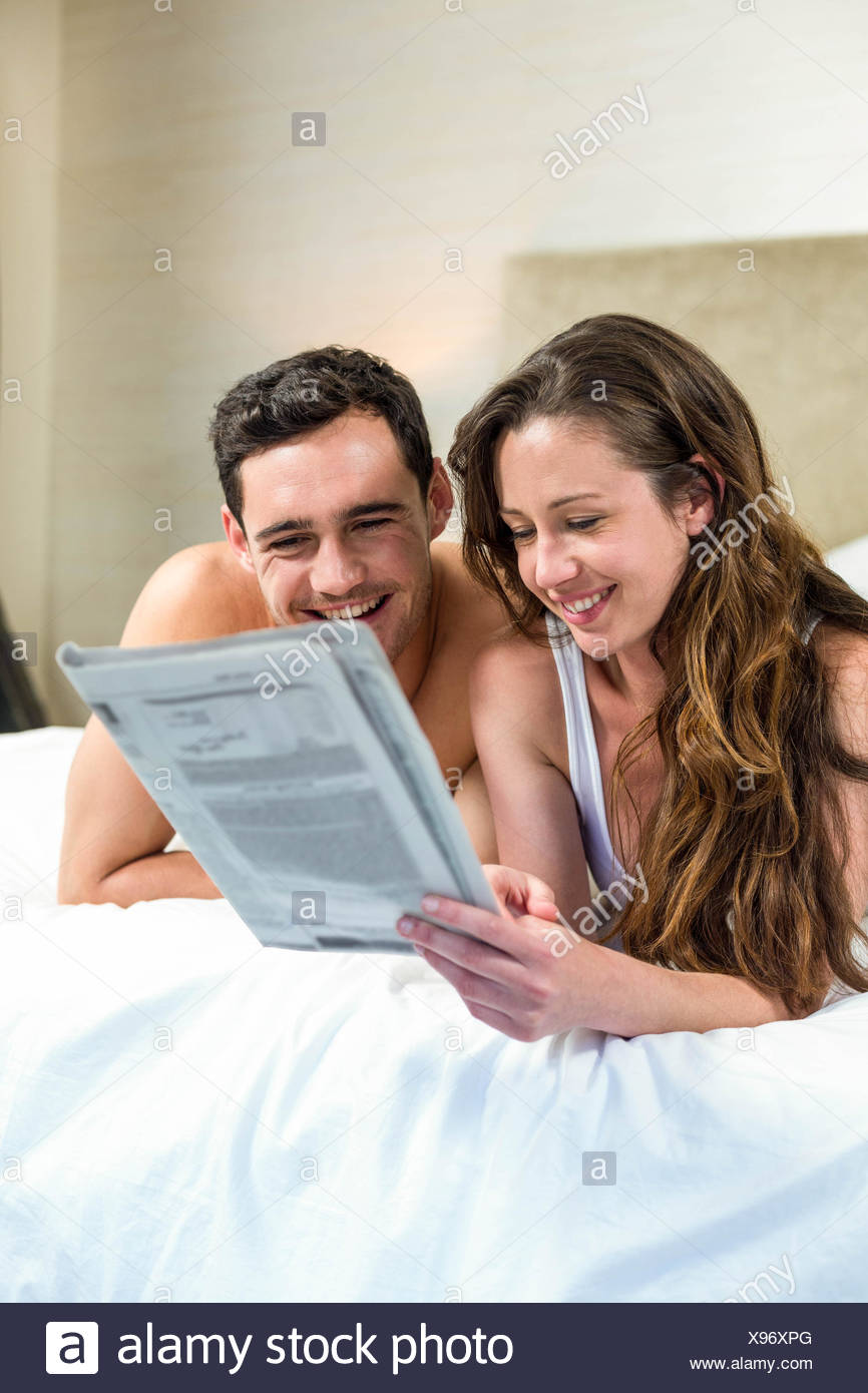Smiling couple lying in bed Stock Photo