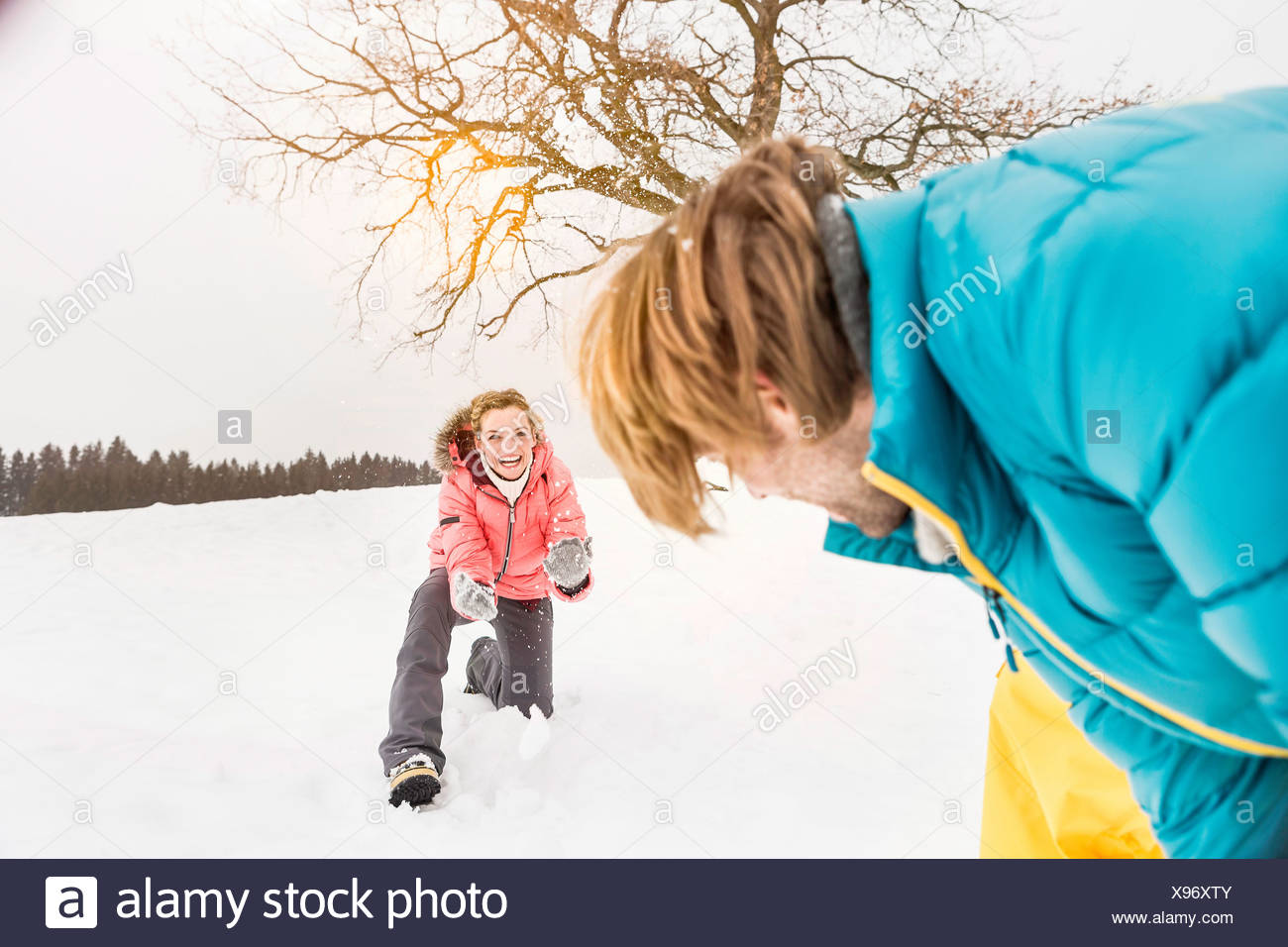 Couple play fighting in snow - Stock Image