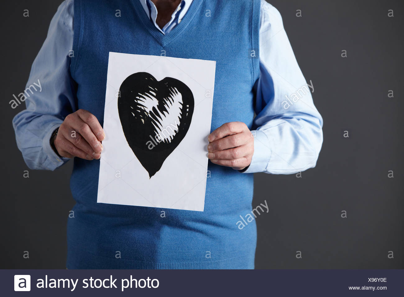 Senior man holding ink drawing of heart - Stock Image
