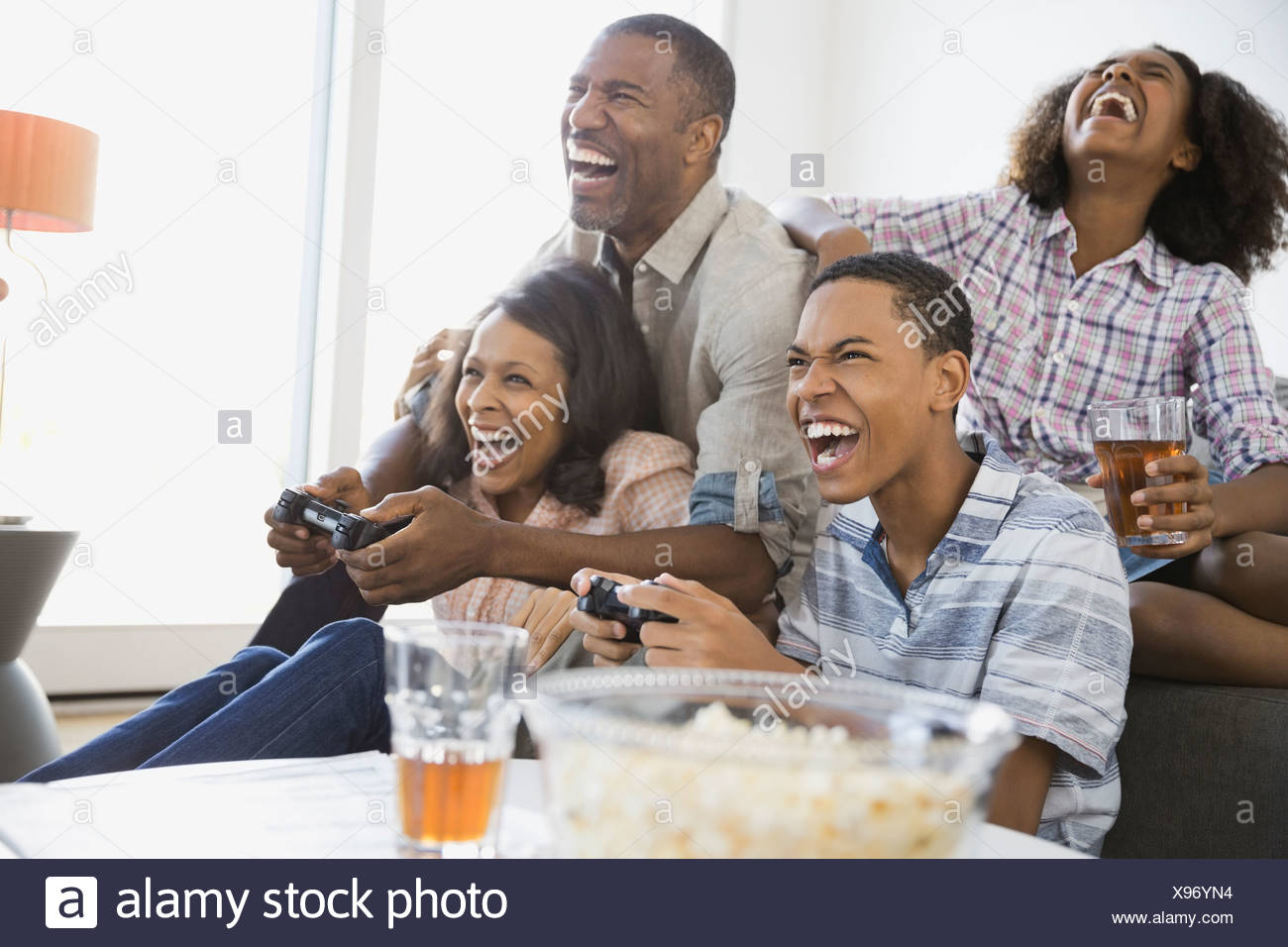 Family playing video games at home - Stock Image